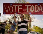 """美国宾夕法尼亚州匹兹堡市一位居民,手持""""请今天去投票""""标识在街上行走。 ( Jeff Swensen/Getty Images)"""