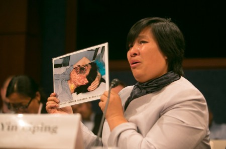 """尹丽萍在听证会上举起了家乡法轮功学员高蓉蓉的照片,说:""""她被中共杀人灭口,再也讲不出来她的故事了,今天我把她带来了。""""(明慧网)"""