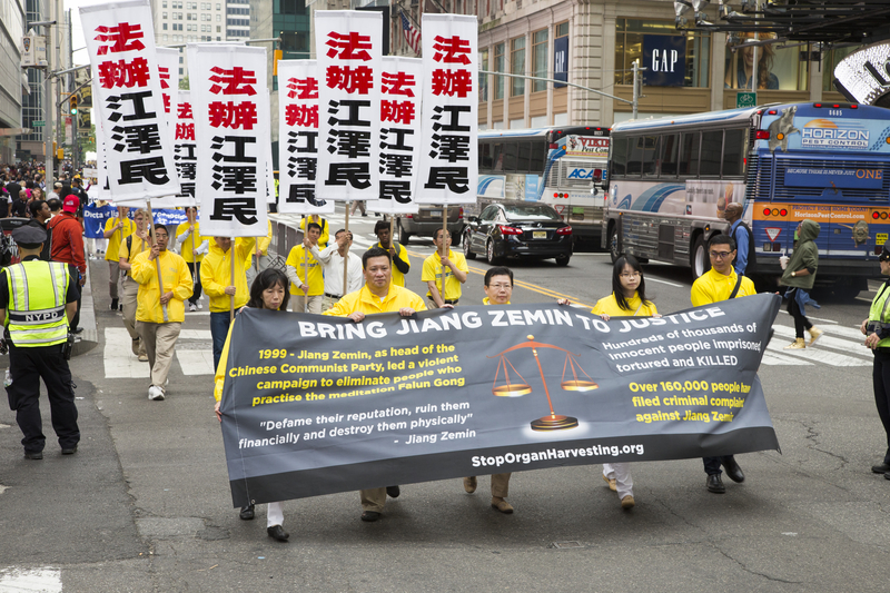 2016年5月13日,紐約上萬人舉行橫貫曼哈頓中心42街的盛大遊行,慶祝第17屆法輪大法日。圖為法輪功學員打出要求法辦江澤民的中英文條幅。(季媛/大紀元)
