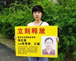 圖:楊臻手持展板要求中共釋放包括她母親在內的法輪功學員。(大紀元圖片)