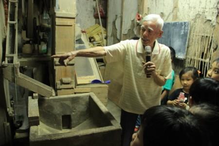 徐朝魁为小朋友解说碾米过程。(谢月琴/大纪元)