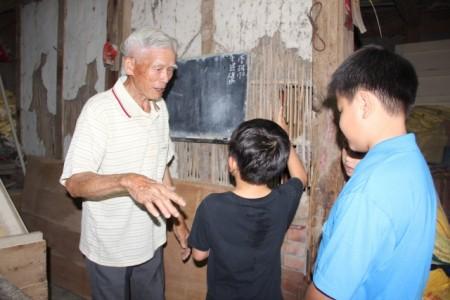 """88岁徐朝魁为小朋友诉说""""牛屎壁""""的故事。(谢月琴/大纪元)"""