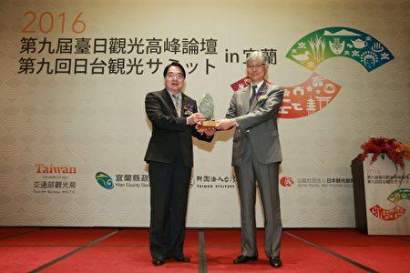 交通部观光局局长谢谓君(左)、日本观光厅参与的本保芳明交换纪念品。(宜兰县政府提供)