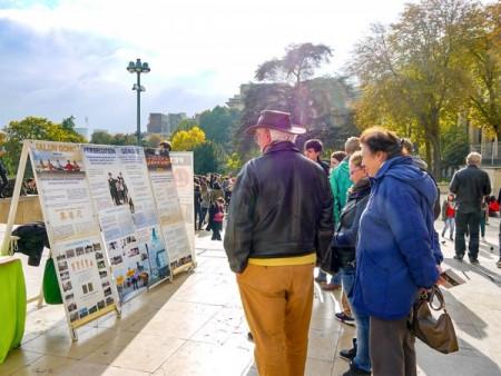 巴黎埃菲尔铁塔下,游客认真阅读法轮功真相展板。(明慧网)