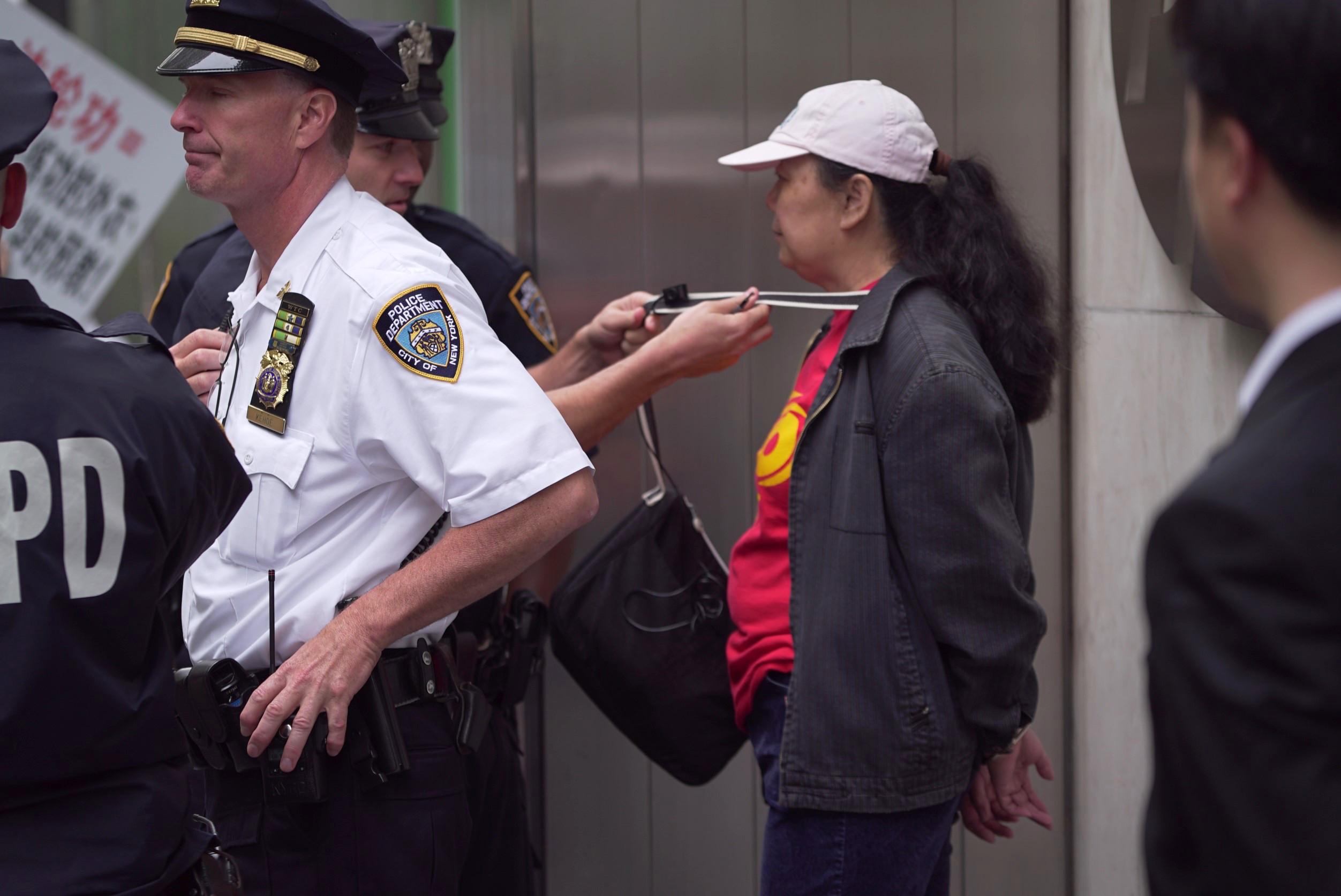 2016年5月13日,李華紅(中)因為干擾法輪功的活動被紐約警察當場拘捕。(大紀元)