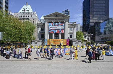 2016年5月8日,溫哥華藝術館前,法輪功學員慶賀法輪大法日,路人紛紛駐足觀看,被現場祥和美好的場面吸引。(攝影:大宇/大紀元)