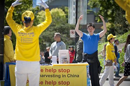 溫哥華藝術館前,溫哥華法輪功學員在表演歡快活潑的傳統腰鼓,來歡慶世界法輪大法日。(攝影:大宇/大紀元)