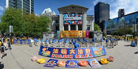 溫哥華部分法輪功學員彙集在藝術館前慶祝法輪大法日。圖正中,一排法輪功學員手中在展示卑詩省的國會議員和市長們發來的賀信和褒獎狀。(攝影:大宇/大紀元)
