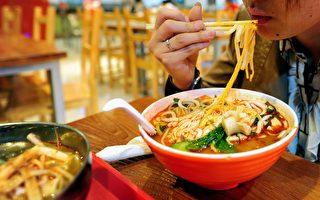 在中國大陸,許多餐館及食品製造商,在食物中添加有毒的化學品。圖為一女士在一家餐館吃麵條。 (FREDERIC J. BROWN/AFP/Getty Images)