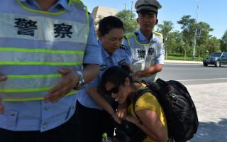 周永康把持政法委时期的中共公安坐大为一股不受制约的暗黑势力,最终在习近平对江派的反击中成为被清洗对象。图为新疆警察在抢夺记者的摄影机。(MARK RALSTON/AFP/Getty Images)
