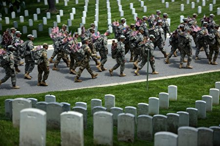 Members of the US Army march with miniature American flags to place at graves in Arlington National Cemetery on May 26, 2016 in preparation for Memorial Day in Arlington, Virginia. / AFP / Brendan Smialowski (Photo credit should read BRENDAN SMIALOWSKI/AFP/Getty Images)