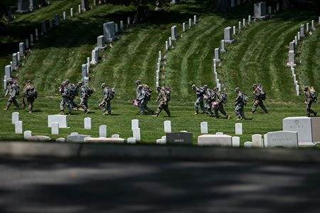 Members of the US Army walk to place American flags at graves in Arlington National Cemetery on May 26, 2016 in Arlington, Virginia in preparation for Memorial Day. / AFP / Brendan Smialowski (Photo credit should read BRENDAN SMIALOWSKI/AFP/Getty Images)