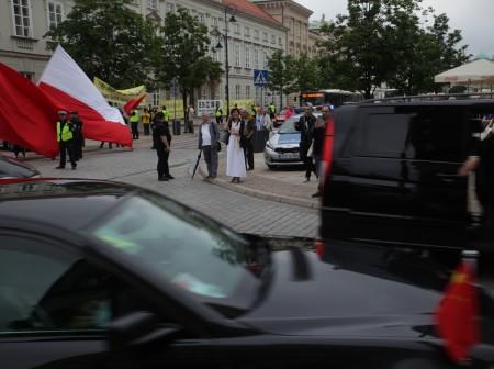 总统府外,习近平车队过来时,江派马仔煽动华人用波兰国旗遮挡法轮功条幅。(黄诃欧/大纪元)