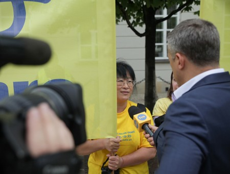 波兰知名电视台TVN记者在总统府外采访了两位法轮功学员并在当天新闻节目中播出。(黄诃欧/大纪元)