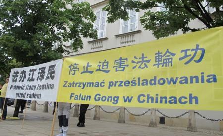 波兰法轮功学员在华沙总统府外面手持条幅,和平请愿。(黄诃欧/大纪元)