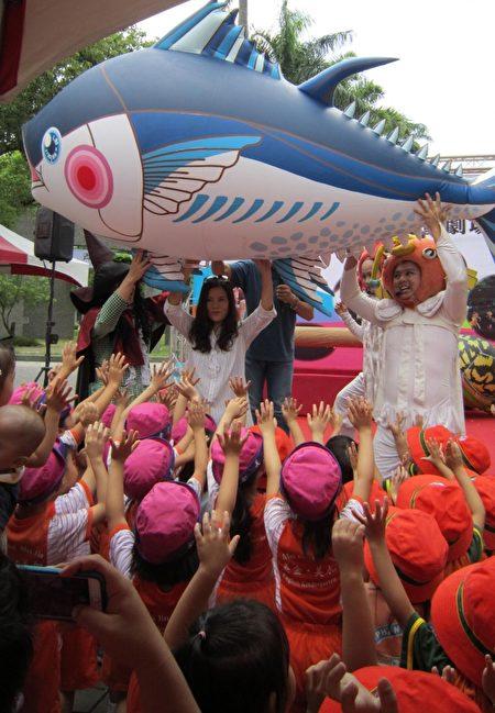 觀光傳播鄞處長和紙風車團員舉起小黑鮪魚氣球,小朋友用手扮演水草,現場歡笑聲連連。(李惠堂 /大紀元)