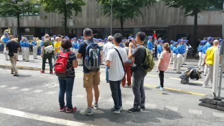 中國留學生觀看法輪功遊行隊伍。(黎平/大紀元)