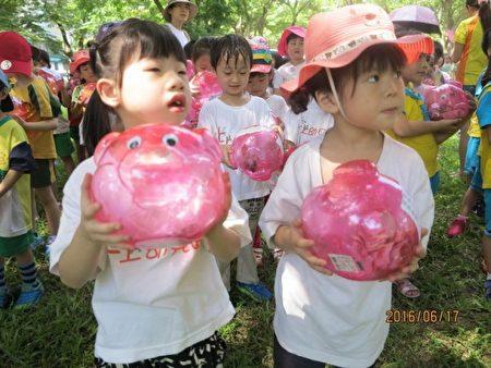 捧著粉紅豬公撲滿的小朋友模樣挺可愛。(新竹縣政府提供)