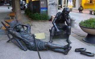 40階梯文化區辛勞的人們在路旁暫時休息片刻。(王知涵/大紀元)