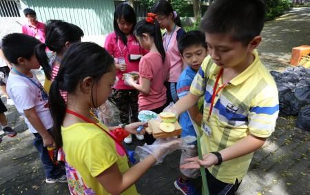 壽山動物園每年暑假推出的兒童營隊課程,受到小朋友喜愛,圖為小朋友幫動物作早餐。(高市壽山動物園提供)