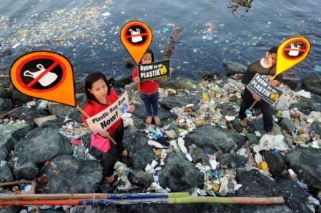 Environmental activists and volunteers hold placards calling for a ban of the use of plastic bags in Manila on July 3, 2014. Volunteers from various environmental advocates collected and separated assorted plastic rubbish polluting Manila Bay and called for national legislation against plastic bags in observance of the 5th International Plastic Bag-Free Day on July 3. AFP PHOTO / Jay DIRECTO (Photo credit should read JAY DIRECTO/AFP/Getty Images)