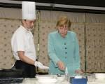 德国总理默克尔2014年访问成都期间观看怎么做宫保鸡丁。   (AFP/Getty Images)