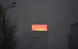 中共大外宣的規模是史無前例的。中共每年花費100億美元在對外宣傳上,遠遠超過美國。 圖為在陰霾籠罩中,北京電子廣告板上的宣傳口號。(GREG BAKER/AFP/Getty Images)