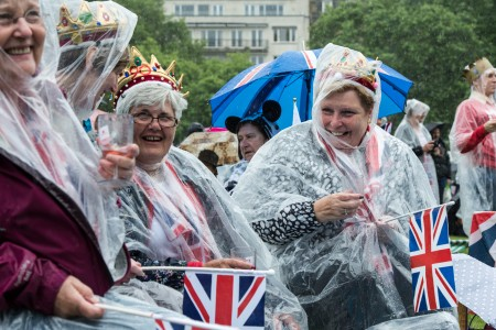 "LONDON, ENGLAND - JUNE 12: (L-R) Isabel Bryce, Sue Withenshaw, Chris Padbury and Eirwen Stevens celebrate together in the rain in Green Park for a picnic and to watch The Queen's Patronage on a big screen during ""The Patron's Lunch"" celebrations for The Queen's 90th birthday on June 12, 2016 in London, England. 10,000 guests have gathered on The Mall for a lunch to celebrate The Queen's Patronage of more than 600 charities and organisations. The lunch is part of a weekend of celebrations marking Queen Elizabeth II's 90th birthday and 63 year reign. The Duke of Edinburgh and other members of The Royal Family are also in attendance. During the lunch a carnival parade will travel down The Mall and around St James's Park. (Photo by Chris Ratcliffe/Getty Images)"