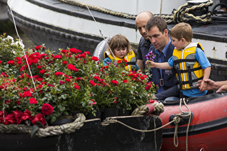 2016年6月22日,英国伦敦,英国遇刺女议员乔·考克斯的丈夫布兰登携二名稚子,以鲜花悼念亡妻。(Dan Kitwood/Getty Images)