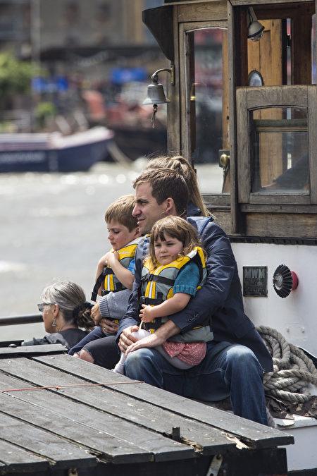 2016年6月22日,英国伦敦,英国遇刺女议员考克斯的丈夫乔·携二名稚子坐船准备参加纪念活动 。(Dan Kitwood/Getty Images)