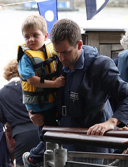 2016年6月22日,英国伦敦,英国遇刺女议员乔·考克斯的丈夫 Brendan Cox抱着儿子Cuillin 登船。(LEON NEAL/AFP/Getty Images)