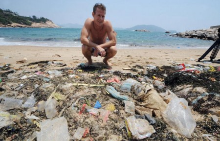 """TO GO WITH Environment-US-Asia-ocean-waste-plastic,FEATURE by Guy Newey Doug Woodring, an entrepreneur and conservationist who lives in Hong Kong, looks at rubbish on May 07, 2009 on a beach on the south side of Hong Kong which has been left uncleaned. A group of conservationists and scientists is due to set sail for an obscure corner of the Pacific Ocean in the coming months to explore a vast swirl of waste known as the """"Plastic Vortex."""" The giant gloop -- which some scientists estimate is twice the size of Texas -- has been gradually building over the last 60 years as Asia and the United States tossed their unwanted goods into the ocean. AFP PHOTO/MIKE CLARKE (Photo credit should read MIKE CLARKE/AFP/Getty Images)"""