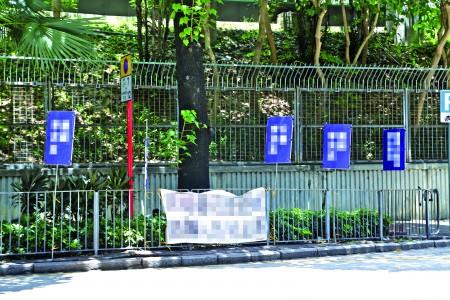 從7月18日晚起,突然出現不明來歷人士,在場館左側泉章居餐廳外欄杆上懸掛約十塊污衊展板。(大紀元)
