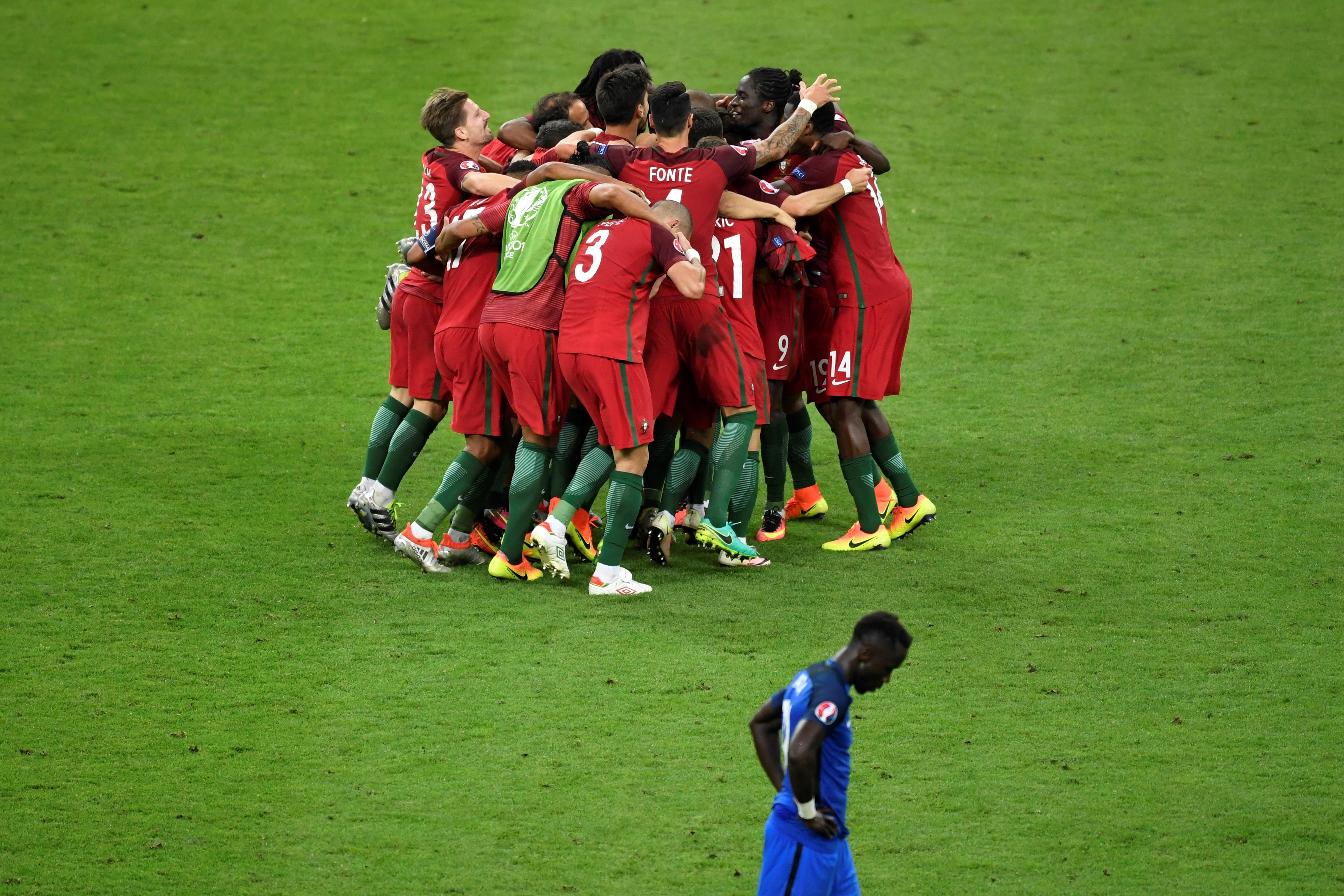 葡萄牙球員擁抱慶祝勝利,與法國球員的表情形成強烈的對比。(MIGUEL MEDINA/AFP)