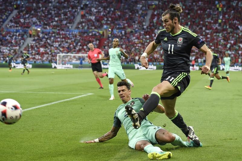 圖為葡萄牙後衛荷西方迪(左)與威爾斯前鋒加里夫巴利(右)在比賽中爭球。(PHILIPPE DESMAZES/AFP)