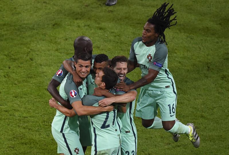 葡萄牙前鋒C.朗(左)入球後和隊友擁抱。(PHILIPPE DESMAZES/AFP)