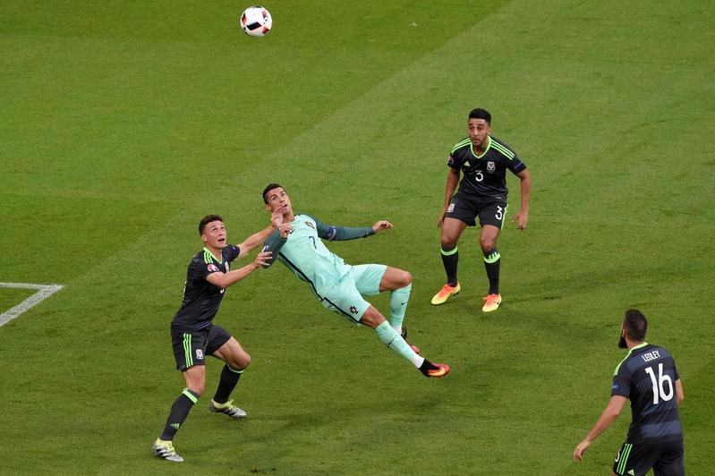 威爾斯後衛占士謝斯達和葡萄牙的前鋒C.朗在比賽中爭球。(PHILIPPE DESMAZES/AFP)