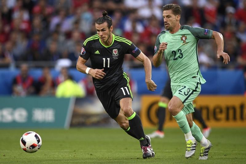 威爾斯前鋒加里夫巴利和葡萄牙的中場球員艾迪恩施華在比賽中。(PHILIPPE DESMAZES/AFP)