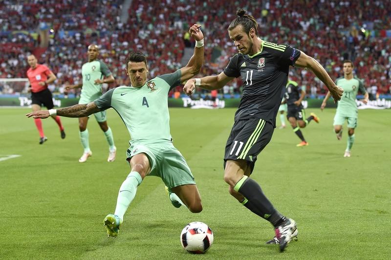 圖為葡萄牙的後衛荷西方迪和威爾斯球員加里夫巴利在比賽中。(PHILIPPE DESMAZES/AFP)