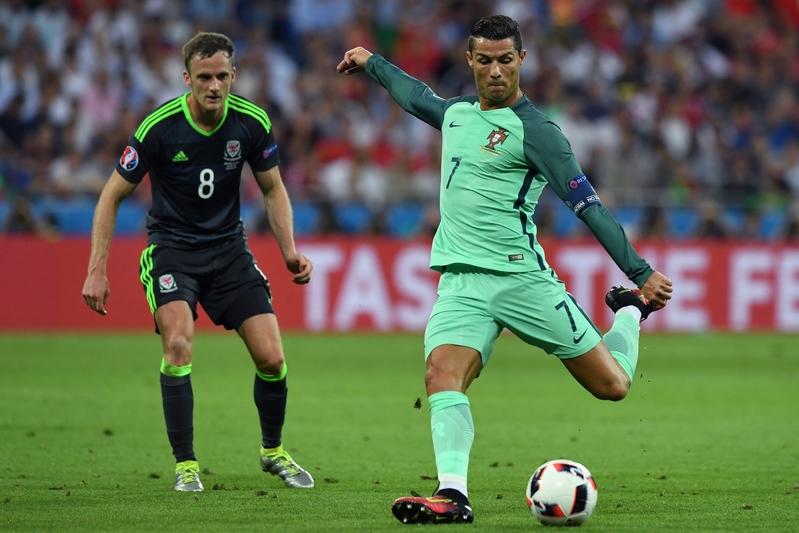 2016年歐國盃第一場半決賽7月6日在里昂球場展開,葡萄牙以2球輕取威爾斯。圖為葡萄牙隊的C. 朗(右)準備射門。(PHILIPPE DESMAZES/AFP)