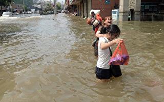 2016年7月7日,湖北武漢,暴雨過後,道路遭洪水淹没,民眾涉水行走。 (STR/AFP/Getty Images)