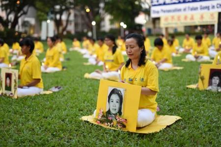图为参加纪念720集会的新加坡部分法轮功学员烛光悼念被中共迫害致死的同修。(Tony/大纪元)