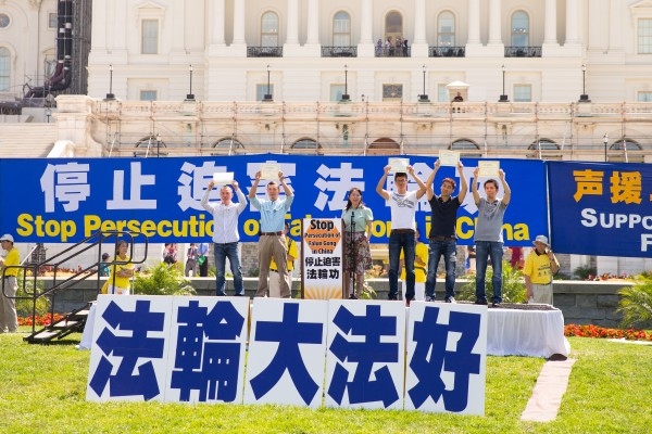 """9位华人分成两批先后走上主席台,他们接过由""""全球退党服务中心""""颁发的退出中共党(团、队)证书,高举起来,面向人群。主席台下响起一片掌声。这一幕将写入历史。(戴兵/大纪元)"""