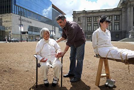 溫哥華藝術館前,法輪功學員進行活摘器官模擬演示,行人駐足觀看、攝影,希望向全世界發佈,幫助宣傳真相。(攝影:大宇/大紀元)