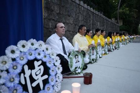 2016年7月19日晚,大温知名博主沃特森(左一)来到中领馆前,加入法轮功学员的烛光悼念。(摄影:大宇/大纪元)
