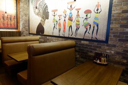 圖:現代風格的餐廳室內設計,牆上掛著富有南非風情的畫作。(李芝毓/大紀元)
