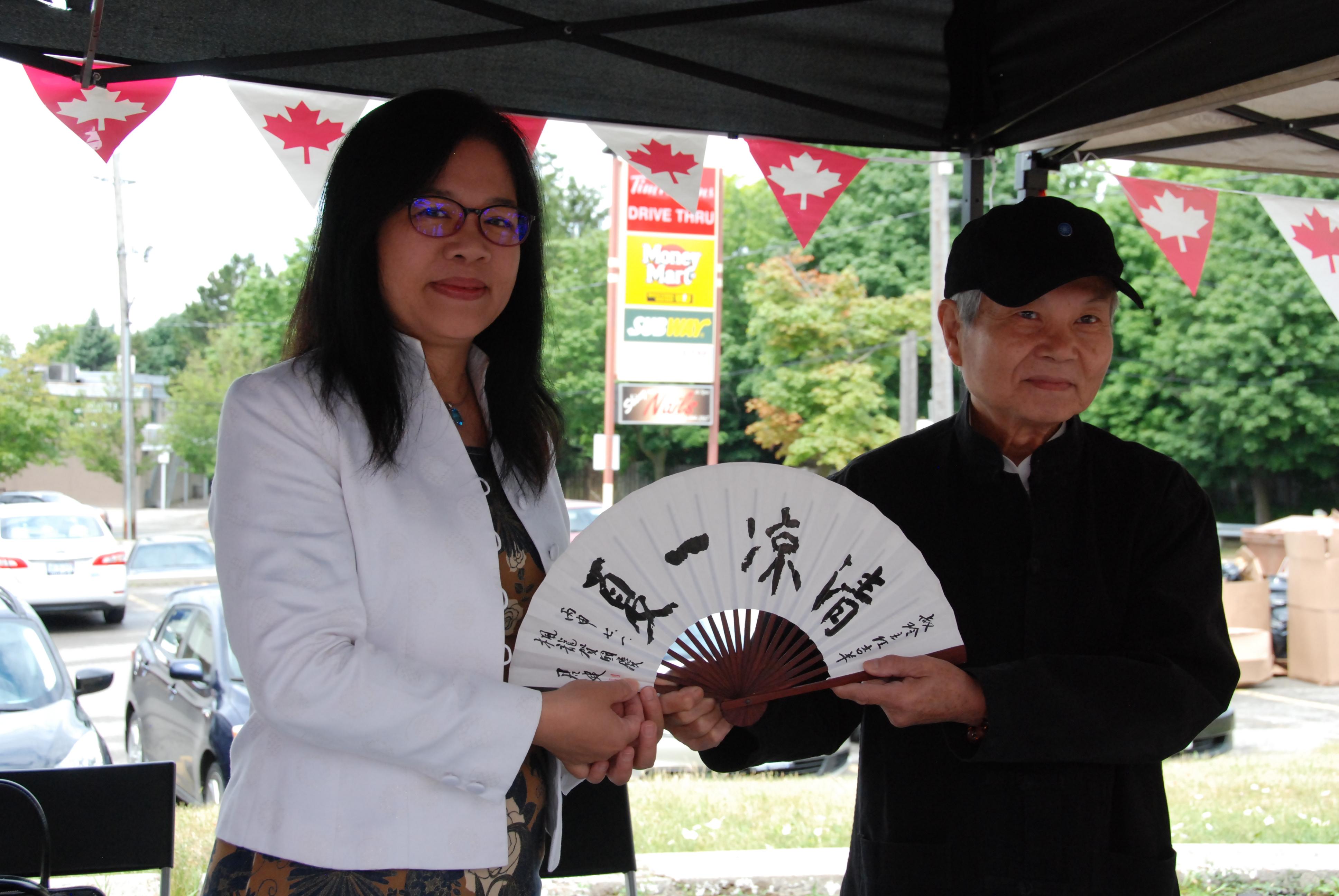 僑領許君健先生(右)為駐多倫多臺北經濟文化中心李叔玲主任贈紙扇。(伊鈴/大紀元)