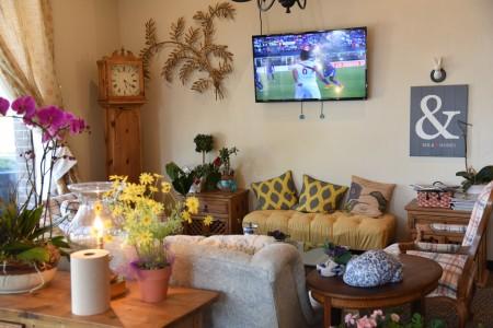 迦南廚坊舒適的軟沙發、木製的桌子及大鐘,佈置十分清新溫暖。(石嵐/大紀元)