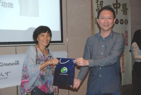 贊助商Erum Science的首席顧問黃連發先生頒發獎品於中獎的幸運兒。(張建浩/大紀元)