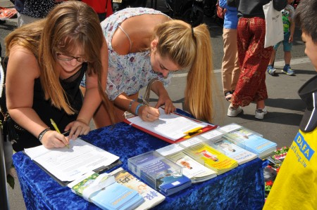 兩位年輕女士在征簽表上簽名,支持法輪功學員。(金湖/大紀元)